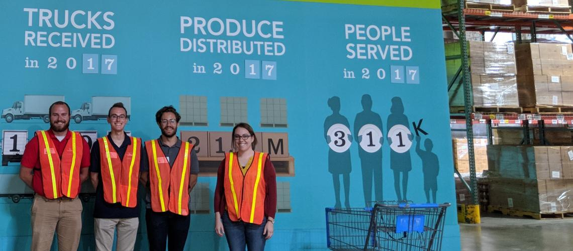 Collin (center) and his project team mates Nate (left) and Ryan (right), tour a local food distribution center with tour guide Haley (far right). The group is posing in front of an informational poster about the distribution center.