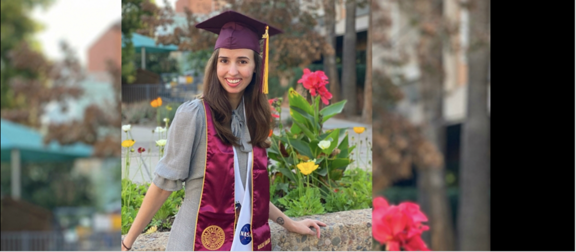 Elinor Saur in graduation cap and sash, posing outside by flowers.