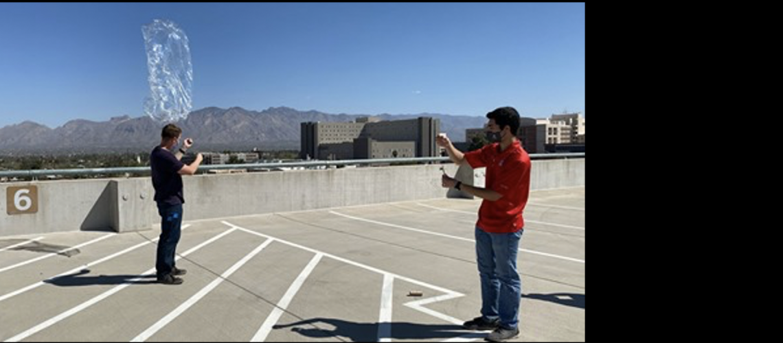 Student, Josh Crest, launchs pico balloon from rooftop.