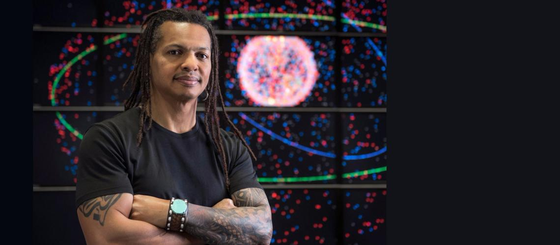 Moriba Jah stands in front of a multi-screen display of orbiting satellites.
