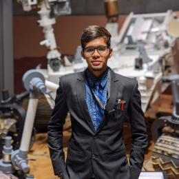 Arsh Nadkarni stands in front of rover model