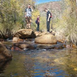 Space Grant students stand on boulders in a creek at Seven Falls, AZ.