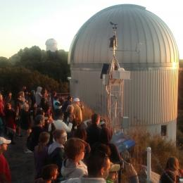 A large group of UA Space Grant Interns, SEDS and Astronomy Club members watch sunset at Kitt Peak Observatory, with telescopes in background.