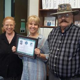 Susan Brew holds award certificate with Dolores and Rick Hill