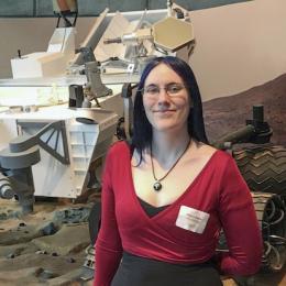 Alexa Drew poses in front of rover model